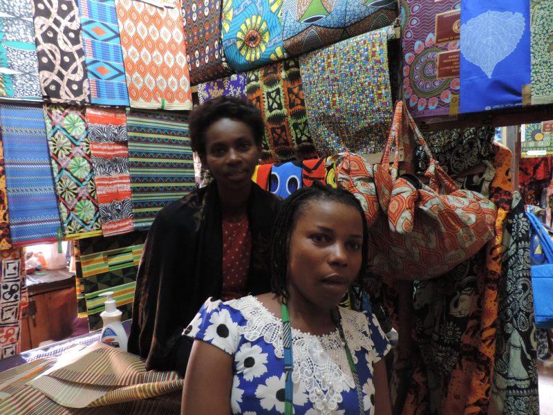 Damerne sidder oppe på bordet i deres lille stofbutik på markedet i Kigali.